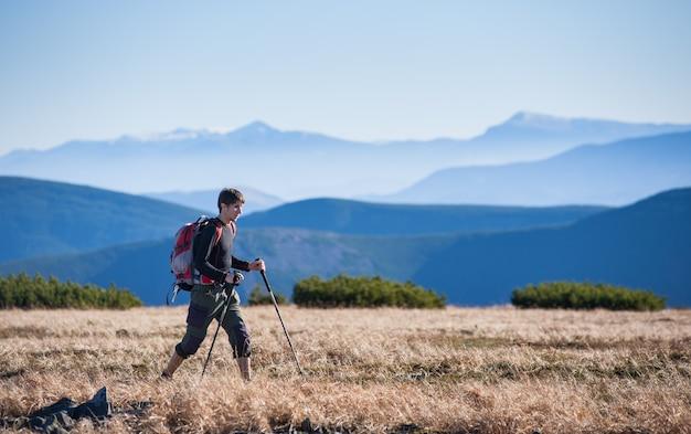 若い観光客は山の小隊の上を歩いています。