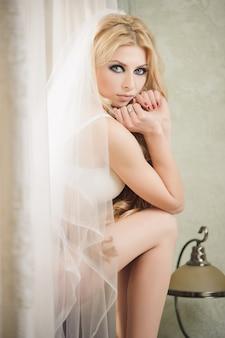 美しい花嫁は結婚式の日にランジェリーとベールを着ています。