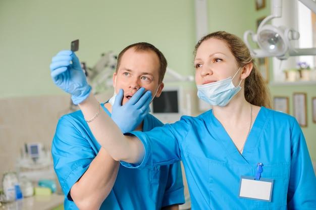 歯科医院で男性の同僚にレントゲンを示す女性歯科医