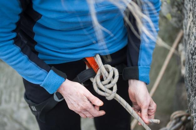ロープの結び目にロープを結ぶ安全ハーネスのクライマー女性