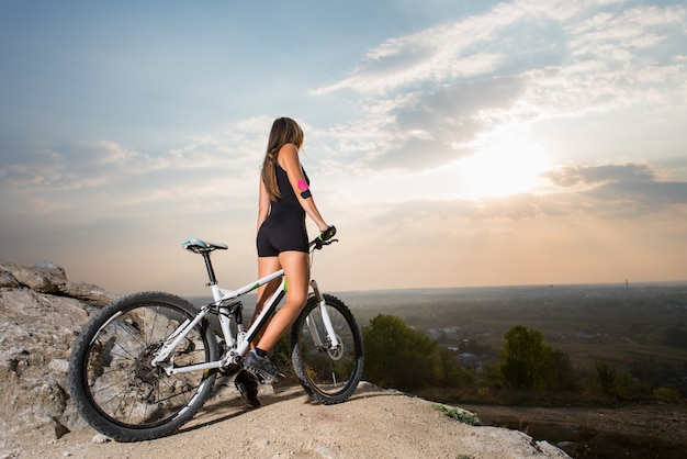 山の丘の上のスポーツ自転車に乗って女性