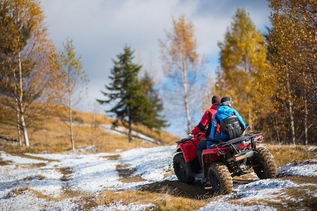雪に覆われた道でクワッドバイクに乗ってカップル