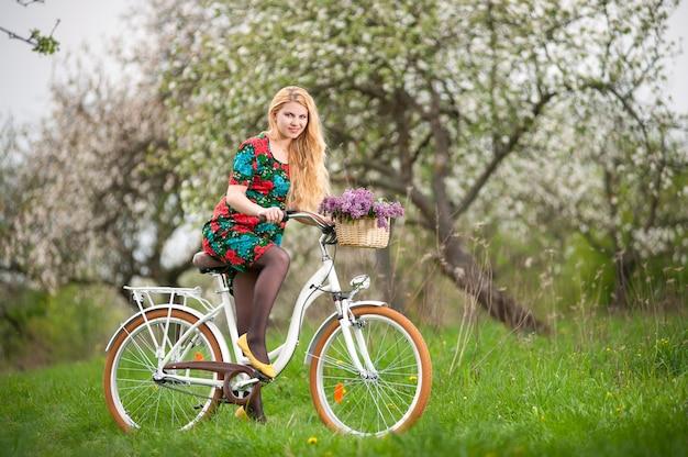 Молодая женщина байкер езда на старинном белом велосипеде