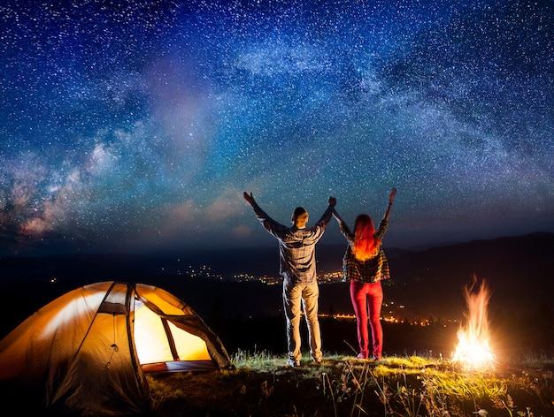 ハイカーはキャンプファイヤーとテントの近くの星の下で手を挙げて夜に星空を見て