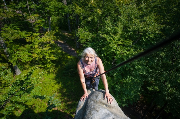笑顔の女性ロッククライマーが岩の上に達しています。登山用具
