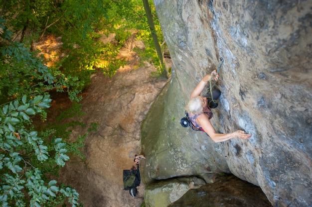 年上の女性ロック・クライマーは、大きな岩の岩壁にカービン銃とロープで登山しています。