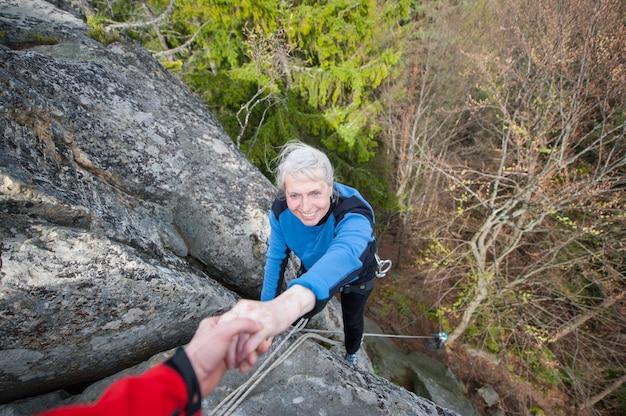 男性のロッククライマーは山の頂上に達するためにクライマーを助けています