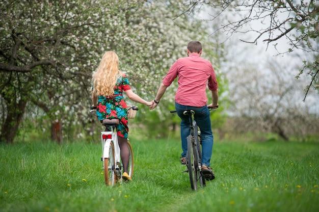 春の庭で自転車に乗ると手を繋いでいる家族