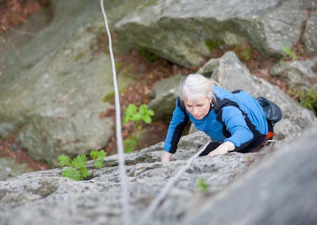 Женщина занимается скалолазанием на скале в горах