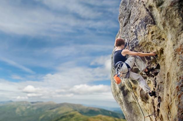 急な張り出して岩崖の上の女性ロック・クライマー