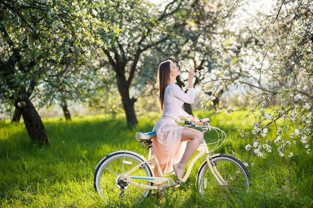 Женщина с ретро-велосипедом в пышной зеленой траве