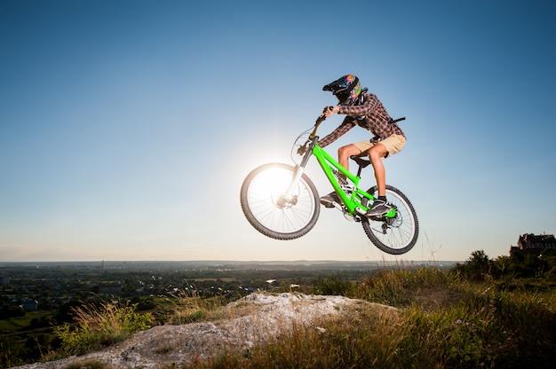 丘の上のマウンテンバイクで下り坂に乗ってサイクリスト