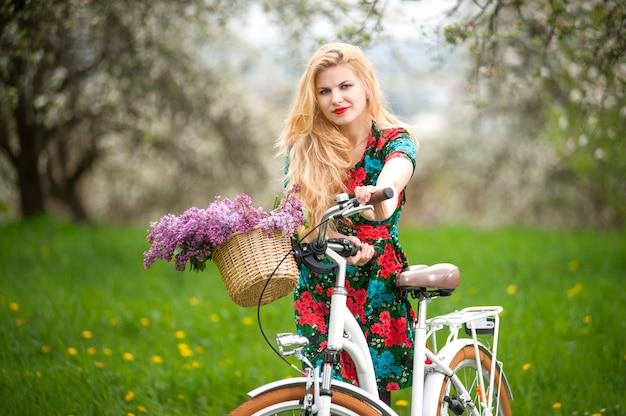 Девушка с винтажным белым велосипедом с корзиной цветов