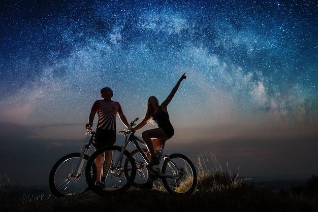 夜の星空の下の丘の上のマウンテンバイクを持つ若い男女。
