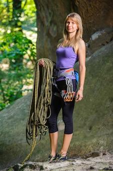 大きな岩の近くにロープを持って女性登山家