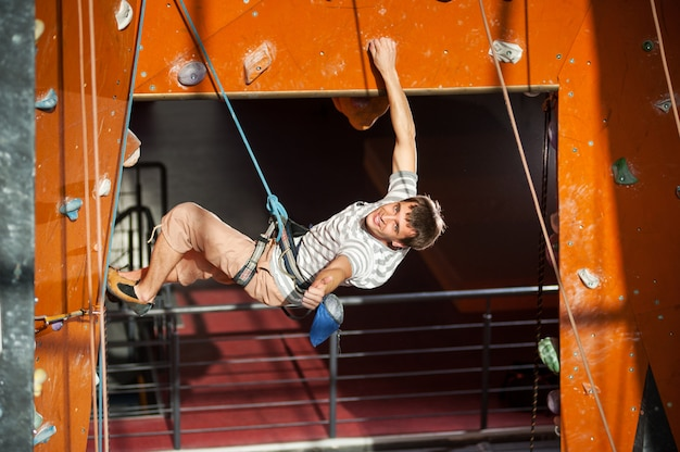 男性のロッククライマーが室内の岩壁で登山を練習
