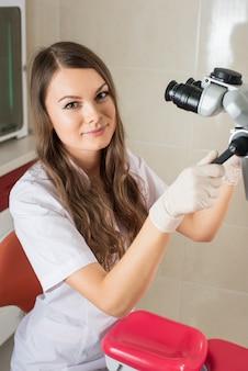 現代の歯科医のオフィスで顕微鏡を持つ魅力的な女医