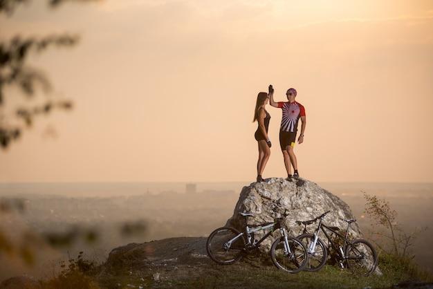 カップルバイカーが岩の上に立っていると、背景をぼかした写真の夏の夜にハイタッチを与えます。