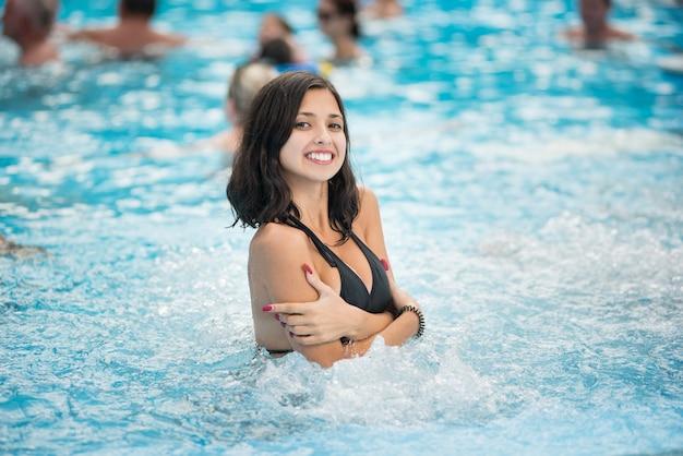 スイミングプールで白雪姫の笑顔と黒の水着の若いブルネットの女性