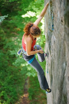 ロープで急な岩を登る美人クライマー