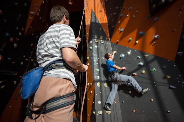 室内の岩壁に登山者を保証するビレイヤー