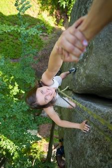 山の頂上に達するために女性の登山者を助けるロッククライマー