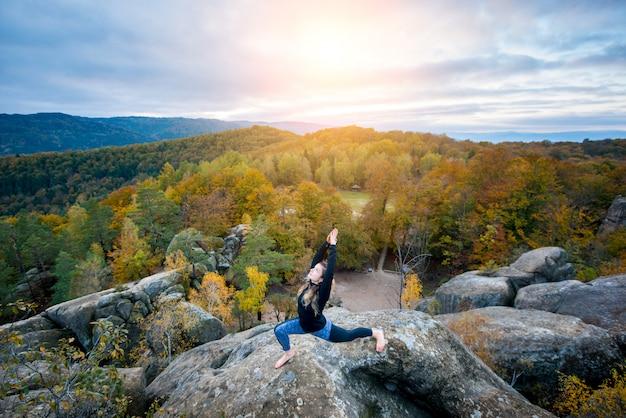スポーティなフィット女性は山の上にヨガを練習します。