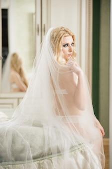 素敵な若い花嫁は白いランジェリーとベールを着て、美しい女性は彼女の寝室のベッドに座っています