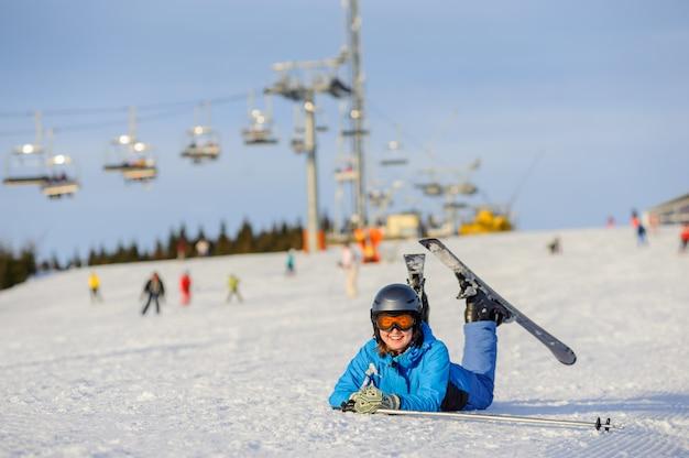 Девушка лыжника лежа на снегу на лыжном курорте в солнечный день