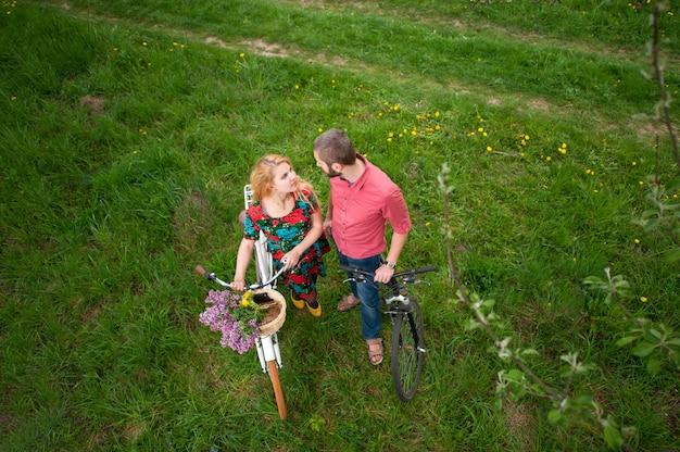 新鮮な緑の芝生を背景にお互いを見て自転車と若いカップル