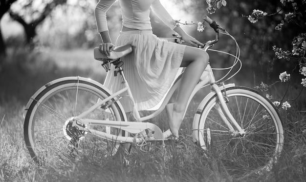自転車に座っている白いドレスのきれいな女性の優雅な曲げ脚のクローズアップ。黒と白