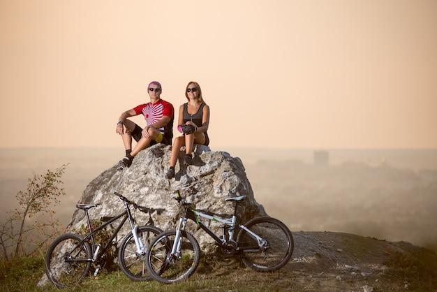 サイクリストはスポーツバイクの隣にある大きな石の上に座っています。