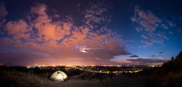 町の近くで夜のキャンプ。全景