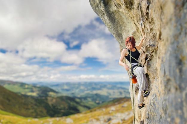 急な張り出した岩の崖のロッククライマー