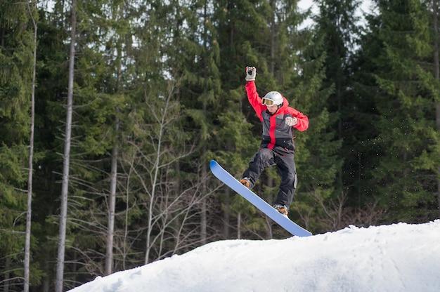 Мужской пансионер на сноуборде летит вниз после прыжка по склону зимой