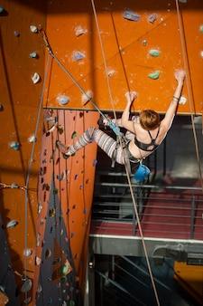 特別な装備を備えた女性登山家が屋内のロッククライミングウォールに登る