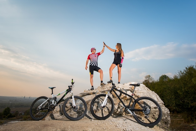 Байкер пара стоит на скале возле велосипеда и дает высокие пять против голубого неба