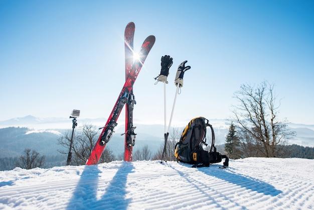 スキー用品のショット-スキー、バックパック、スティック、手袋、一脚上のアクションカメラ