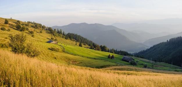 山の風景、農場、納屋、干し草の山々のパノラマ