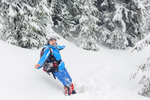 幸せな面白い女の子が雪のドリフトに飛び込む