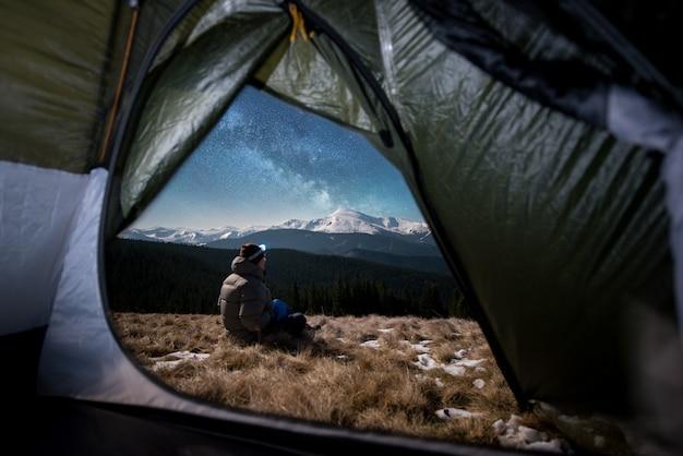 男性のハイカーのテントの中からの眺めは、夜に彼のキャンプで休憩します。