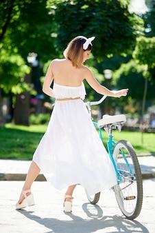 日当たりの良い夏の通りに青い自転車の横にある若い女性から撮影