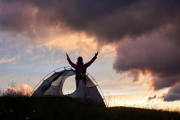 Касаясь неба. женский альпинист, поднимая руки в небо, наслаждаясь удивительным закатом в горах