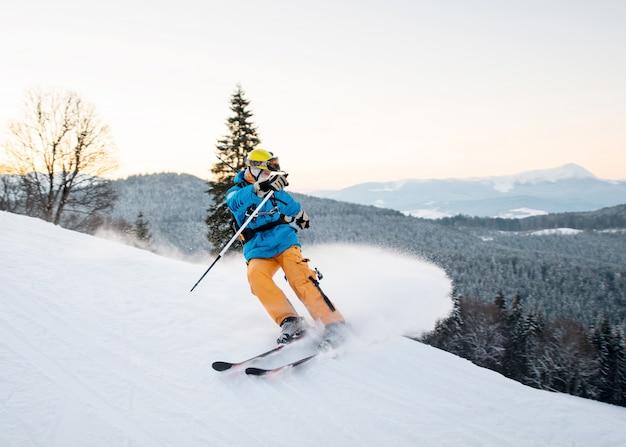 雪粉のスキーヤーの男は山の斜面にブレーキをかけます