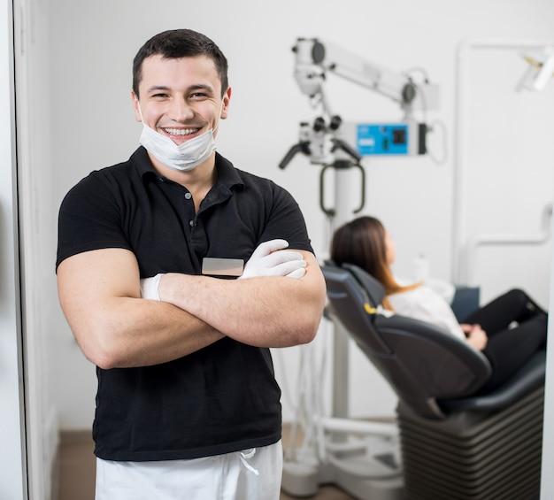 彼の手で立っているセラミックブラケットを持つフレンドリーな男性歯科医は歯科医院で交差しました。口腔病学