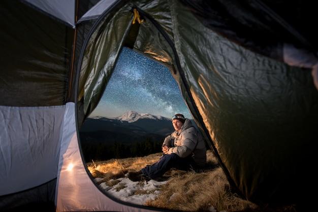 男性観光客は夜の山でのキャンプで休憩します。