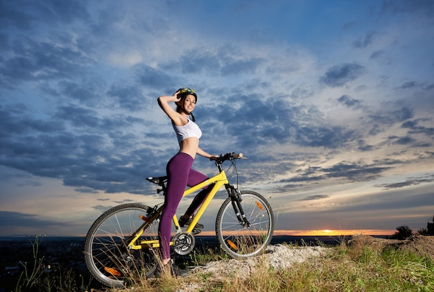 Молодая женщина велосипедист на велосипеде на вершине горы с красивым ландшафтом на закате