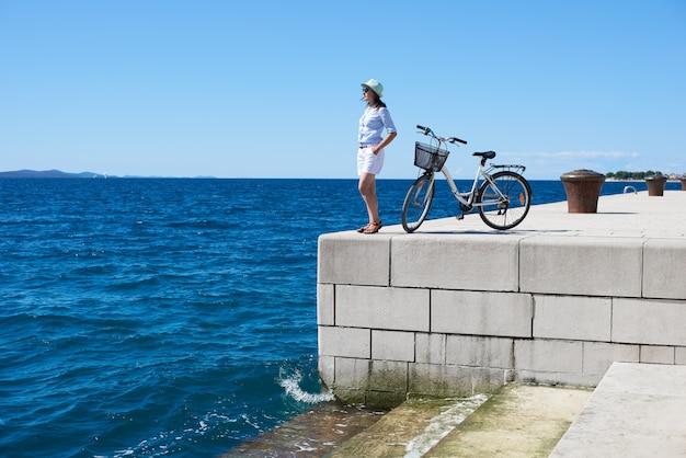 海の近くの若い女性乗馬都市自転車