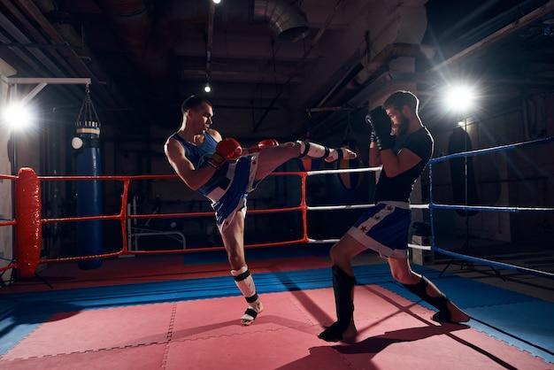 ヘルスクラブのリングでキックボクシングをトレーニングするボクサー