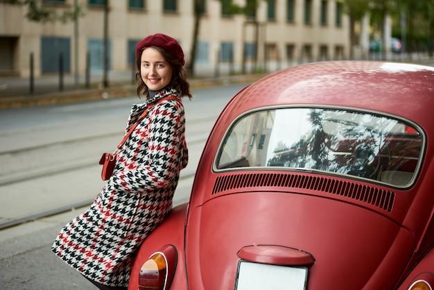 Красный ретро автомобиль позади и милая девушка возле него. крупный план